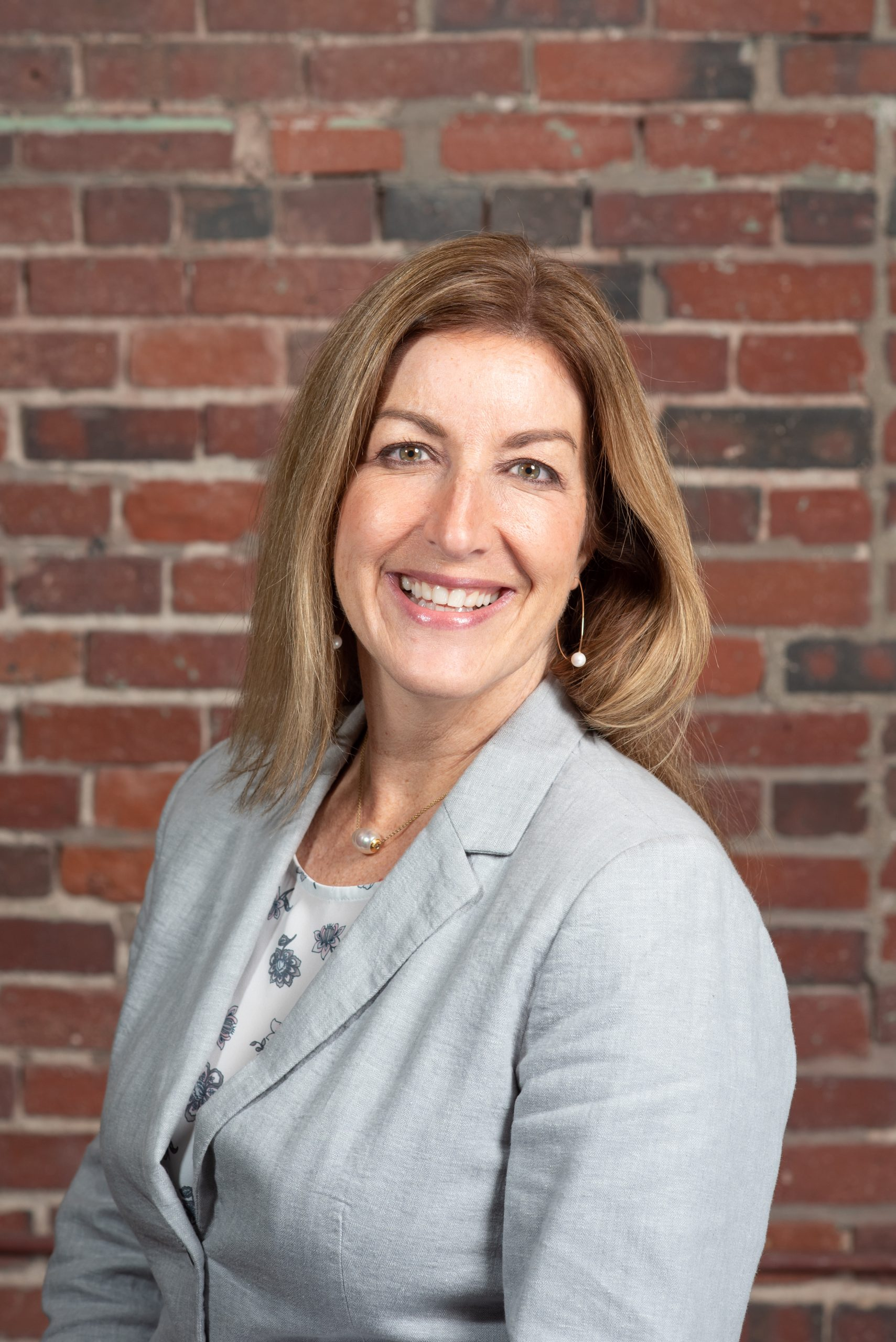 Jen Mayes Chief Sales Officer sitting in front of a brick wall.