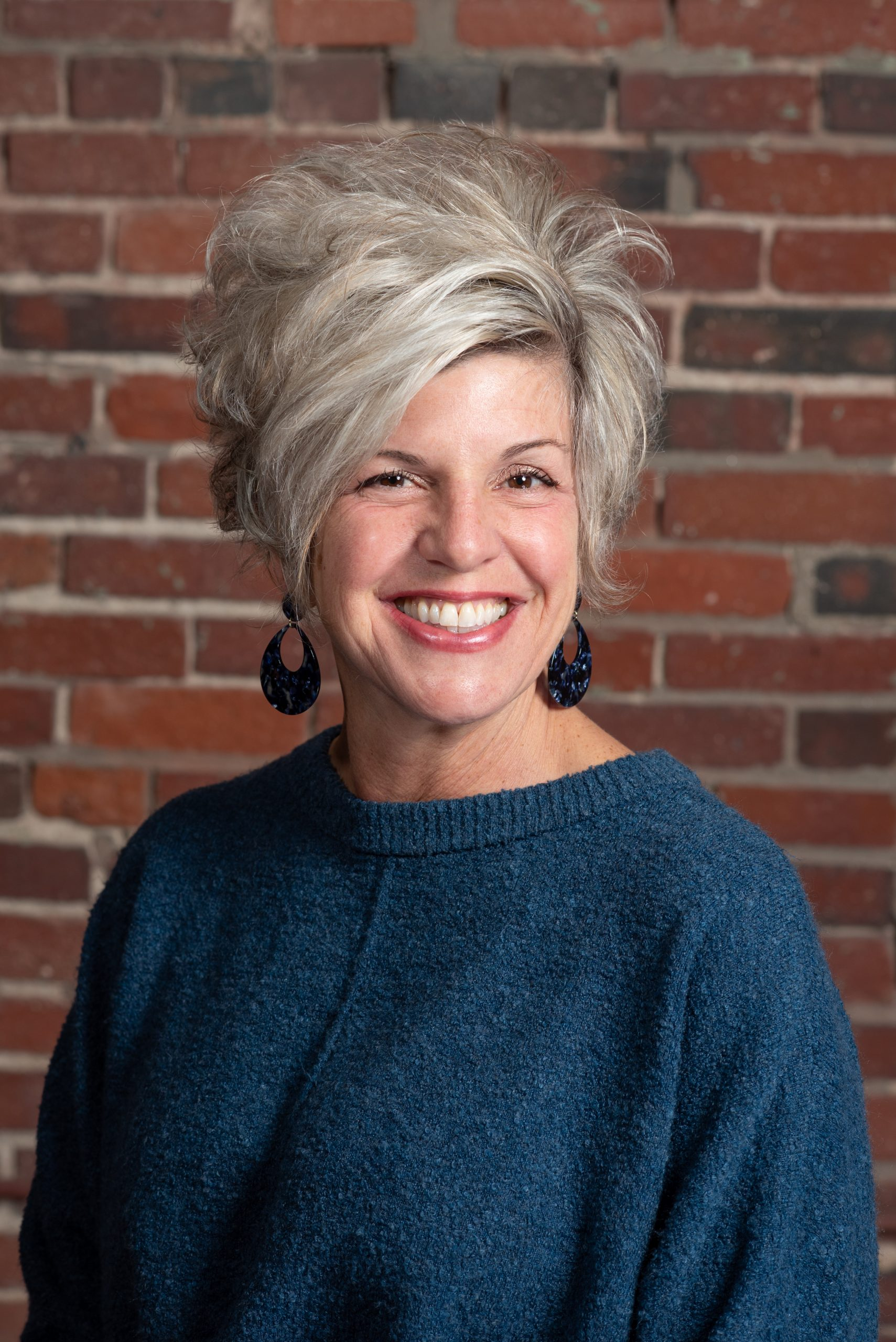 A photo of our executive assistant Gretchen Hubert in front of a brick wall.
