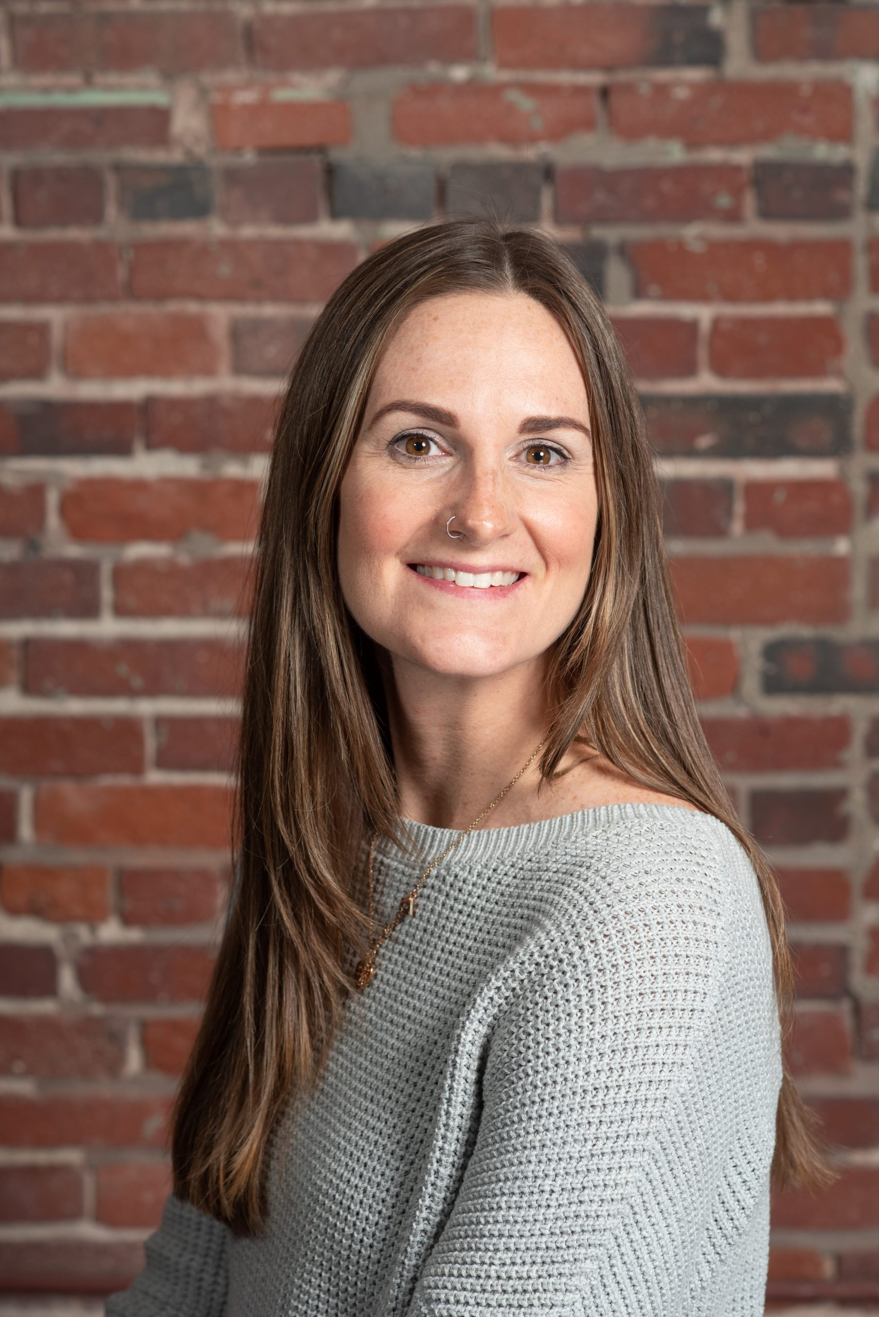 A photo of Noelle Hurley Marketing Communications Manager in front of a brick wall.