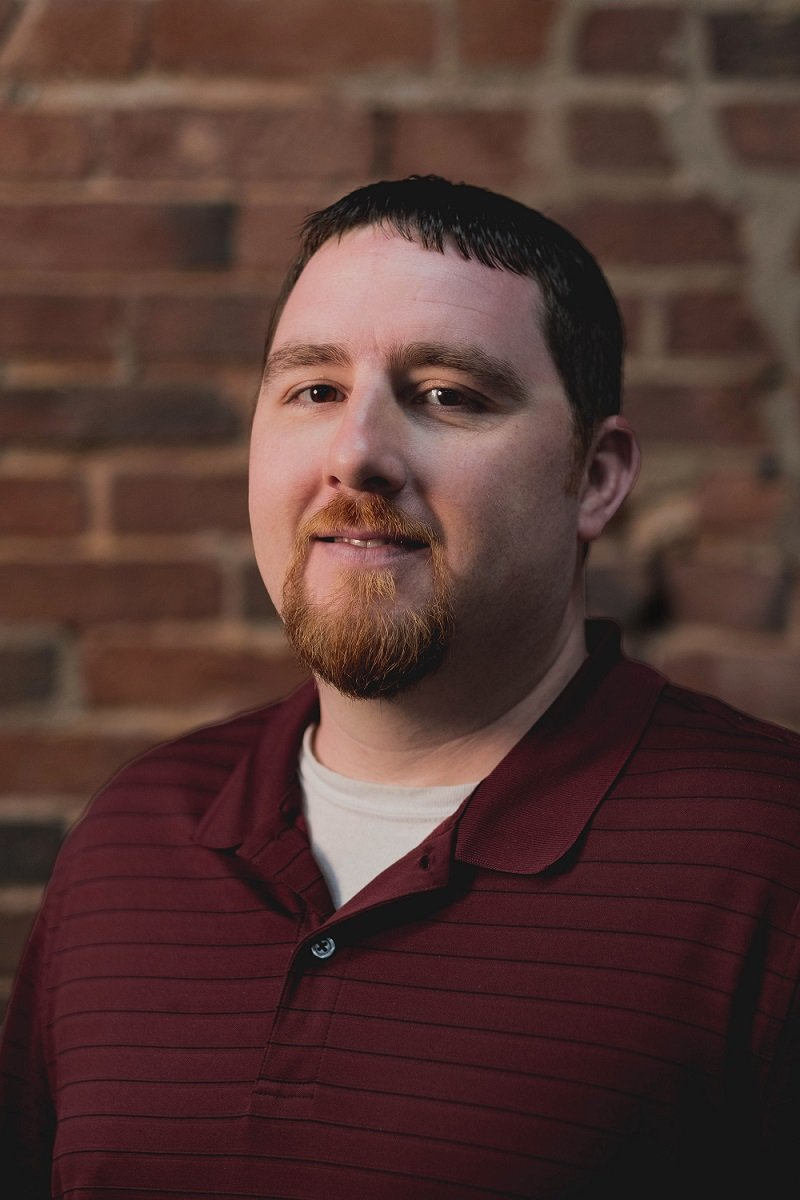Our Warehouse Associate Matt Romano smiling in front of a brick wall.