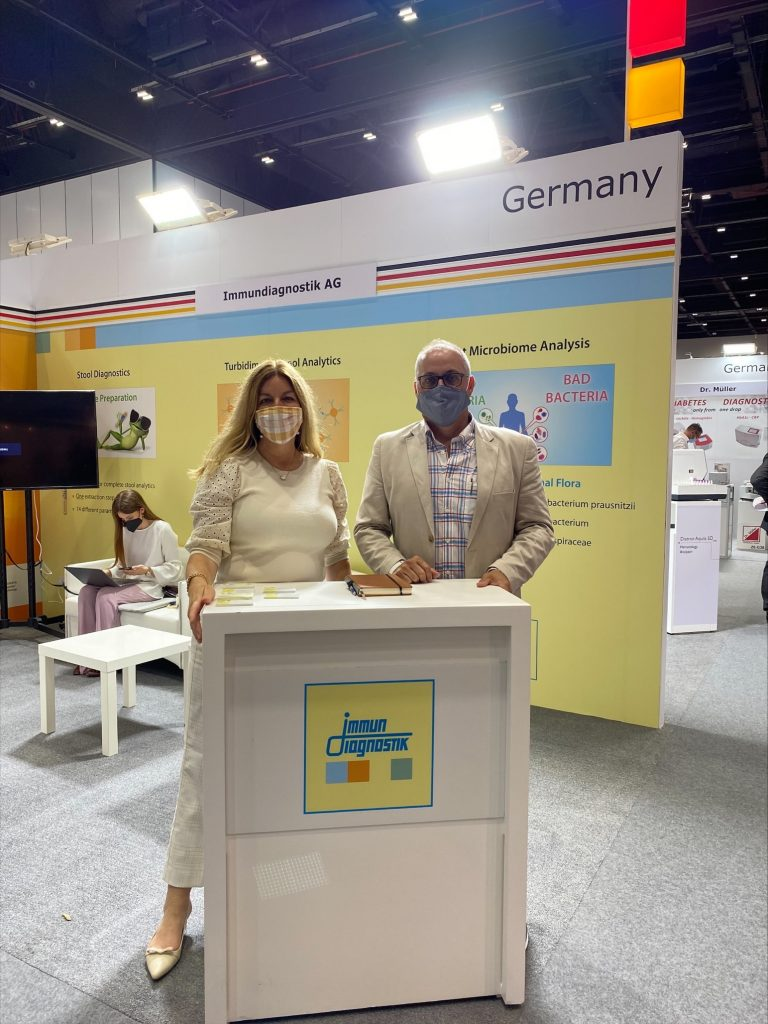 Jen Mayes and Terry Fisher of Immundiagnostik, Inc. wearing masks standing in the Immundiagnostik booth at Medlab Middle East in Dubai.